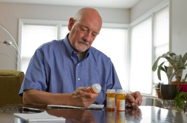 Older man looking through his prescription medications