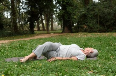 Older woman laying in grass doing quick stretching workout