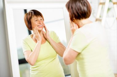 Older woman looks into mirror doing age fighting face exercises