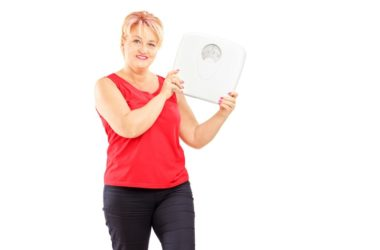 Senior woman holds scale to show successful weight loss beating obesity without counting calories