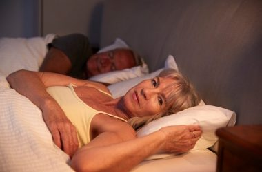 Woman lying awake in bed suffers from insomnia and has higher risk for health problems