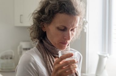 Woman with drinking glass is being exposed to radiation in the water supply