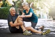 Senior man experiences knee pain as his wife comforts him