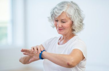 Senior woman embracing health gadgets using fitness tracker