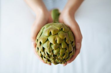 Woman holding an artichoke one of the spring superfoods