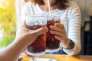 Close up of couple holding glasses of soda linked to pancreatic cancer