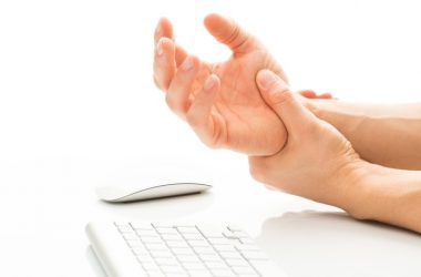 Close up of cramping hands over keyboard from magnesium deficiency