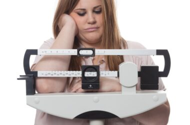 Overweight woman looking at scale trouble losing weight