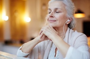 Senior lady with headphones experiencing music health benefits