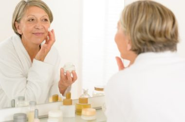Senior woman looking in mirror using bath and body products