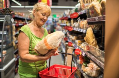 Smiling senior woman shopping for wheat bread