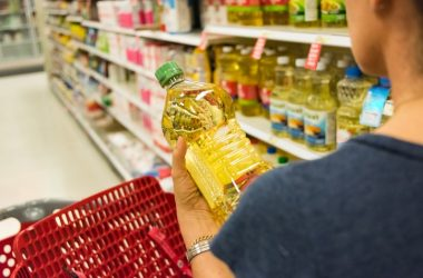 Woman in grocery store holding canola oil bottle