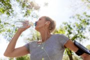 Woman working out outside stops to drink from plastic water bottles