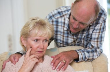 Man comforting senior woman with word finding problem