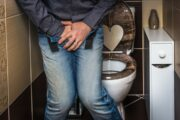 Man in bathroom hands across crotch having prostate symptoms not prostate cancer