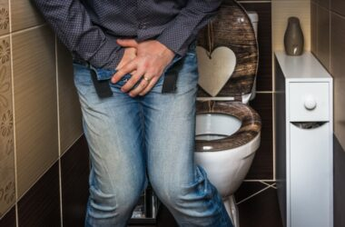 Man in bathroom hands across crotch having prostate symptoms