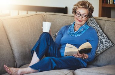 Senior lady sitting on sofa reading to reduce dementia risk