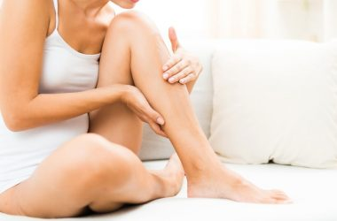 Woman sitting up in bed massaging a painful leg cramp