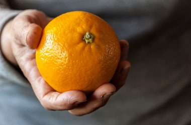 Close up of a hand holding an orange which fights AMD age-related macular degeneration