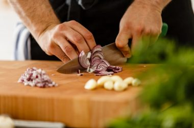Close up of man cutting onions and garlic on a cutting board