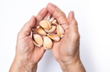 Senior woman holds high blood pressure fighting garlic cloves in hands