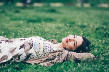 Woman lying in grass relaxing and forest bathing