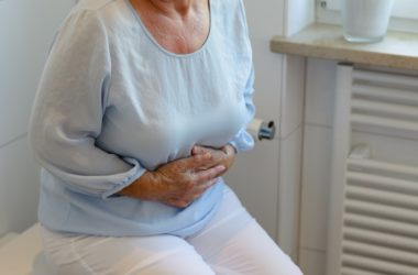 Senior woman sitting in bathroom suffering from constipation and gut inflammation