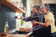 Smiling older couple cook and add spices to food to boost metabolism and fight inflammation