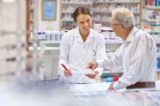 Pharmacist smiles as she offers discounts on prescriptions to a customer