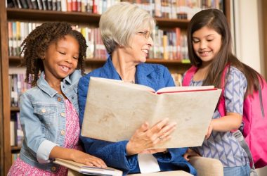 Senior volunteer reading to kids in a library
