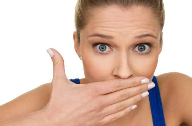 Woman with hand over mouth to cover bad breath