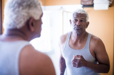 Senior man looking for a heart attack warning sign in the mirror
