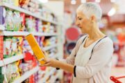 Senior woman reading labels on processed foods for ingredients like fructose