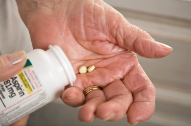 Senior woman with aspirin in hand facing hidden dangers