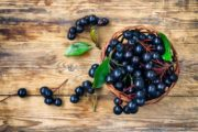 Anthocyanins-rich chokeberry bunches in wicker basket on wooden table