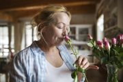 Senior woman using sense of smell to sniff a rose