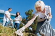 Senior woman volunteer picking up trash working long hours