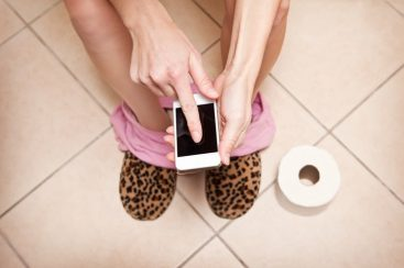 Woman using smartphone while sitting on the toilet