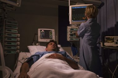 Man trying to sleep in hospital bed with nurse nearby