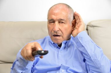 Senior man holding remote has trouble hearing TV