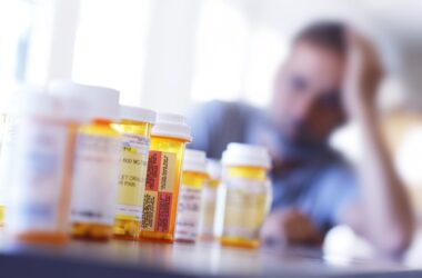 Man with pill bottles full of opioids and painkillers
