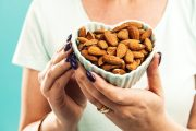 Woman with heart shaped bowl of heart disease fighting almonds