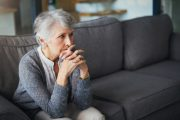 Isolation lonely senior woman sitting on gray sofa