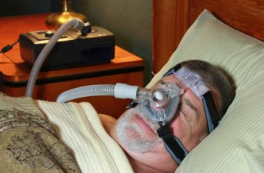 Senior man in bed using CPAP machine for sleep apnea