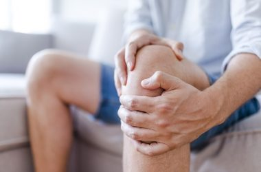 Man massaging his painful knee considers knee surgery