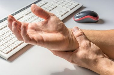 Man with carpal tunnel from typing holds painful wrist