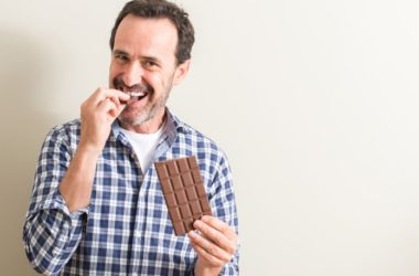 Middle aged man happily eating a square of chocolate
