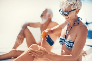 Attractive senior woman in bikini applies sunscreen