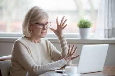 Woman experiencing anger while looking at computer