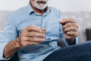 Close up on senior man taking vitamin D supplements to survive cancer